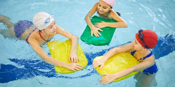 Group of girls having fun and swimming with board together in swimming pool