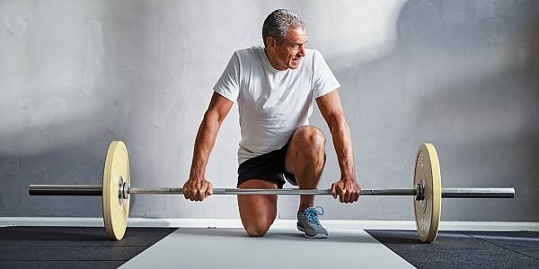 Senior man in sportswear kneeling alone in a gym preparing to lifting weights during a workout